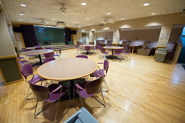 Dance hall style room with small stage, tables with chairs and booths lining the walls.