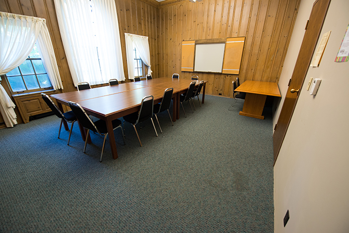 Pine walled room with large conference table and windows.