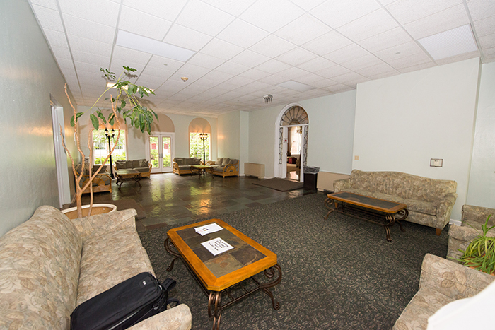 large room with walk through and seating areas on both windowed ends.