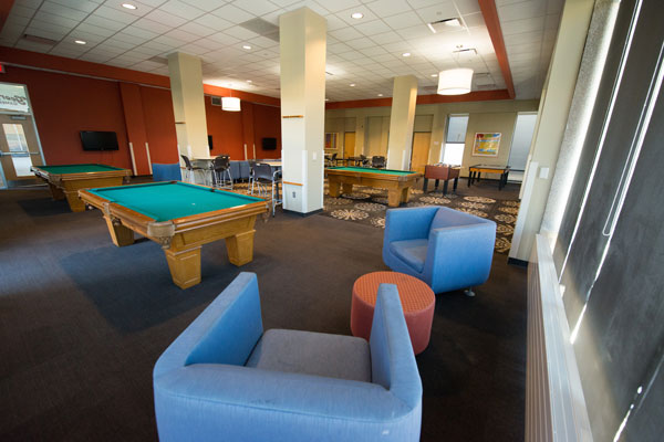 Large room with ample seating, flat screen TVs, pool tables, table tennis table, foosball table.