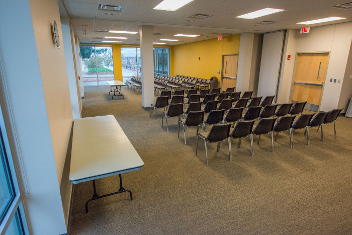 Large room with lots of chairs front table, media cart and ceiling mounted projector.