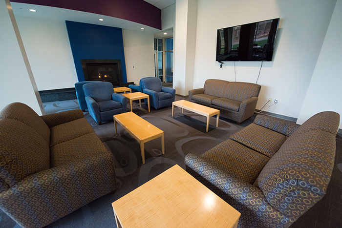 Three sofas and two chairs squared up around a few coffee tables with a large screen TV mounted on one wall.
