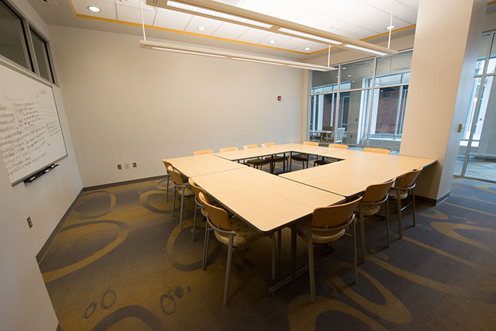 A room with large conference table, plenty of seating and dry erase board.