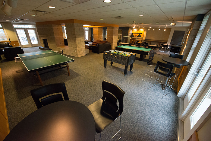 Room with pool table, foosball table and many chairs.