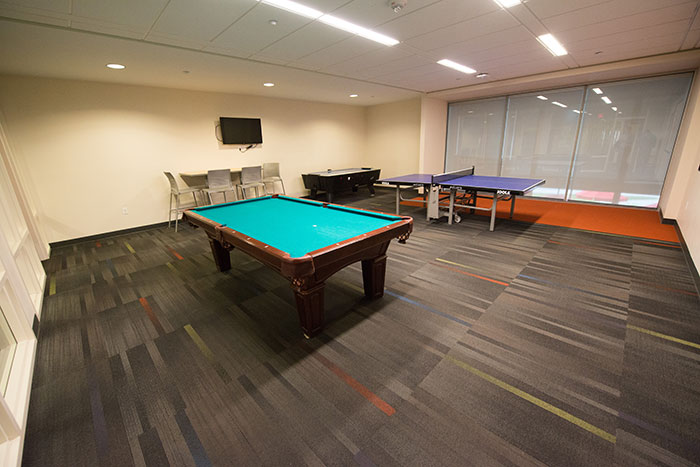 Room with Ping-Pong, air hockey, pool tables, and TVs.