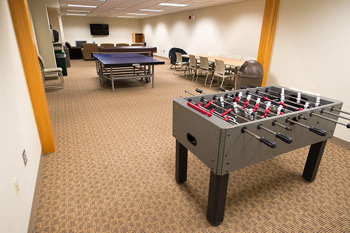 Long rectangular room with TV with seating, ping pong and Foosball tables.