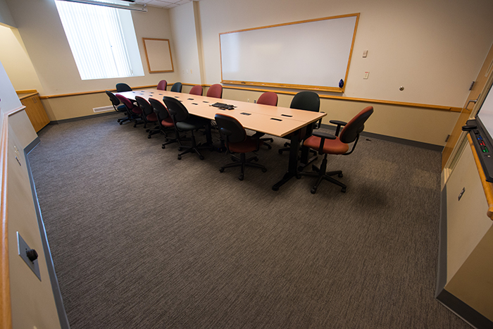 Long room with long conference table, window and dry erase boards.
