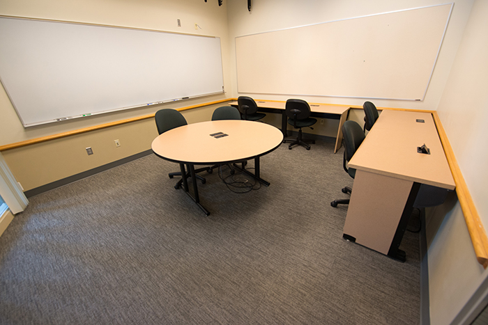Meeting room with dry erase boards mounted on walls and three tables/desks.