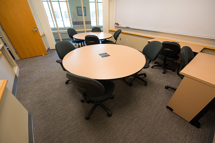 Room with two round tables, two rectangular desks and dry erase boards.