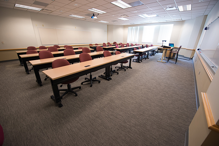 Large classroom like space with table/desks for 32+ people, plus instructors desk and dry erase boards.