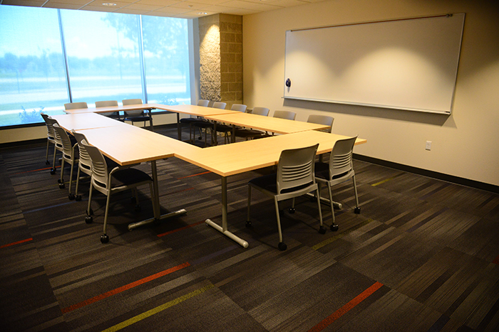 Room with wall of windows, dry erase board and tables/chairs arranged in large rectangle.